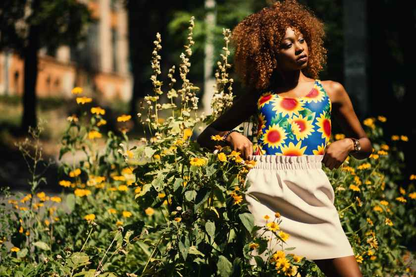 photography of woman wearing blue yellow and red floral tank top standing