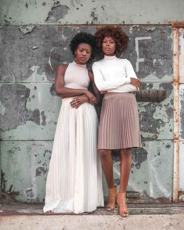 two women standing beside wall at daytime